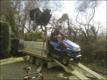 Un tracteur tondeuse vide son bac à pelouses dans une remorque