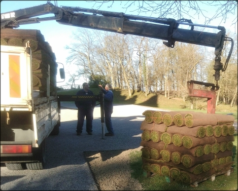 un camion grue décharge des palettes de rouleaux de gazons