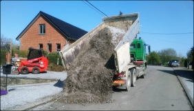 Un camion conteneur qui décharge des gravas